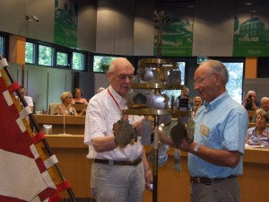 Cor Rops (r) hangt samen met Wim van Rooij het schildje van de Heemdagen 2014 in Roosendaal en Essen aan de schellenboom
